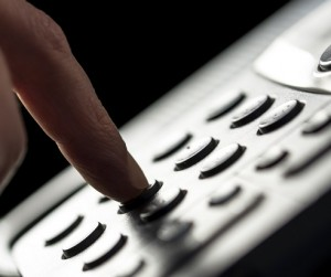 Closeup of the finger of a businessman making a call on a landline telephone pressing the buttons on the keypad to dial the number.