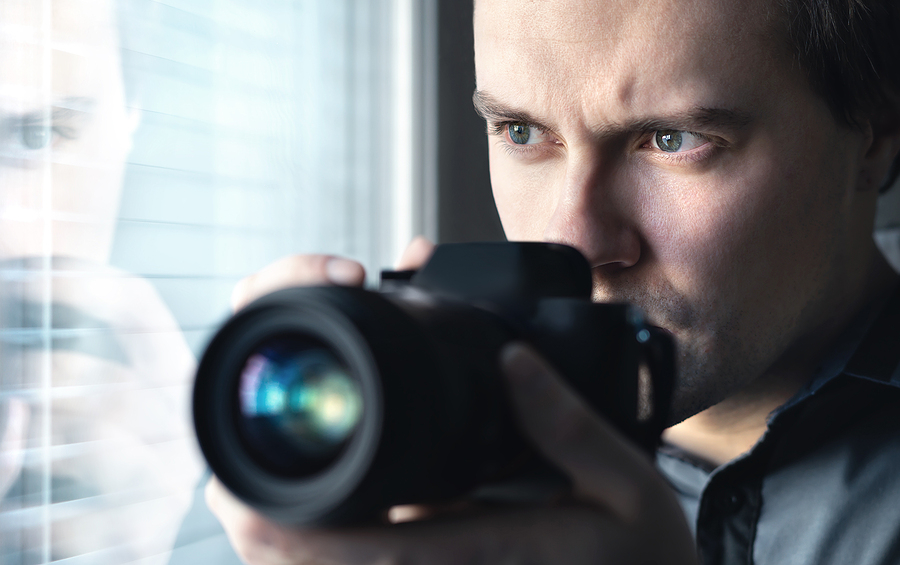 Private Investigator Holding a Camera and Looking from the Window